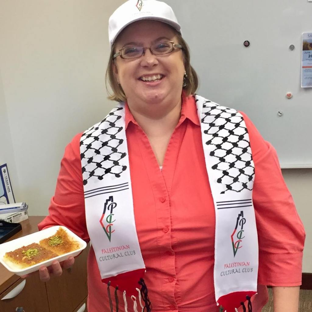 Amy holding food at Palestinian Cultural Club event