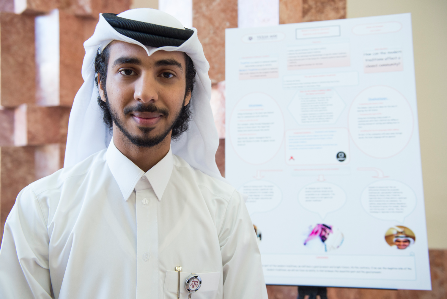 Arabic student  in Qatar next to school project poster