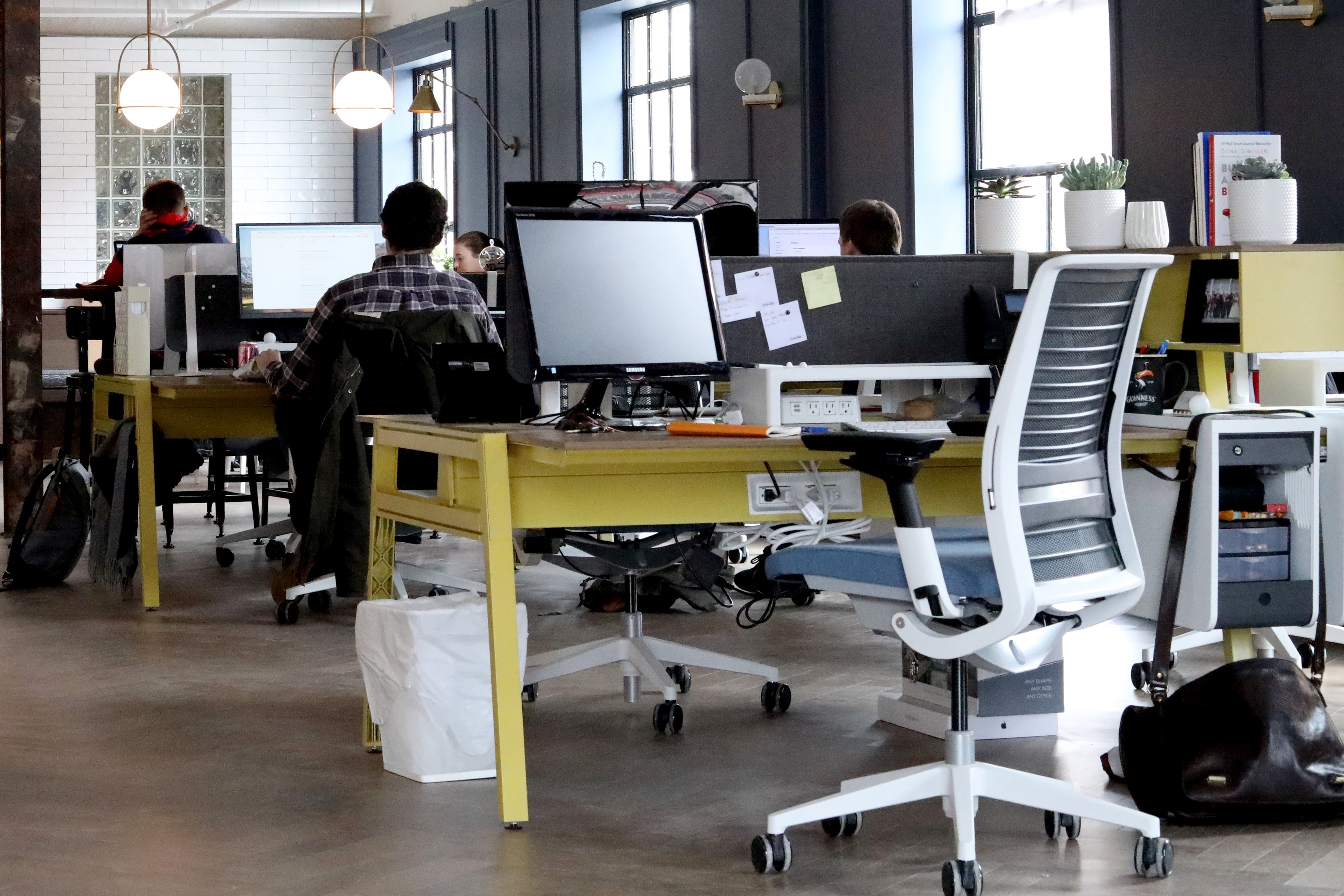 Modern office space with computers and yellow desks and rolling chairs