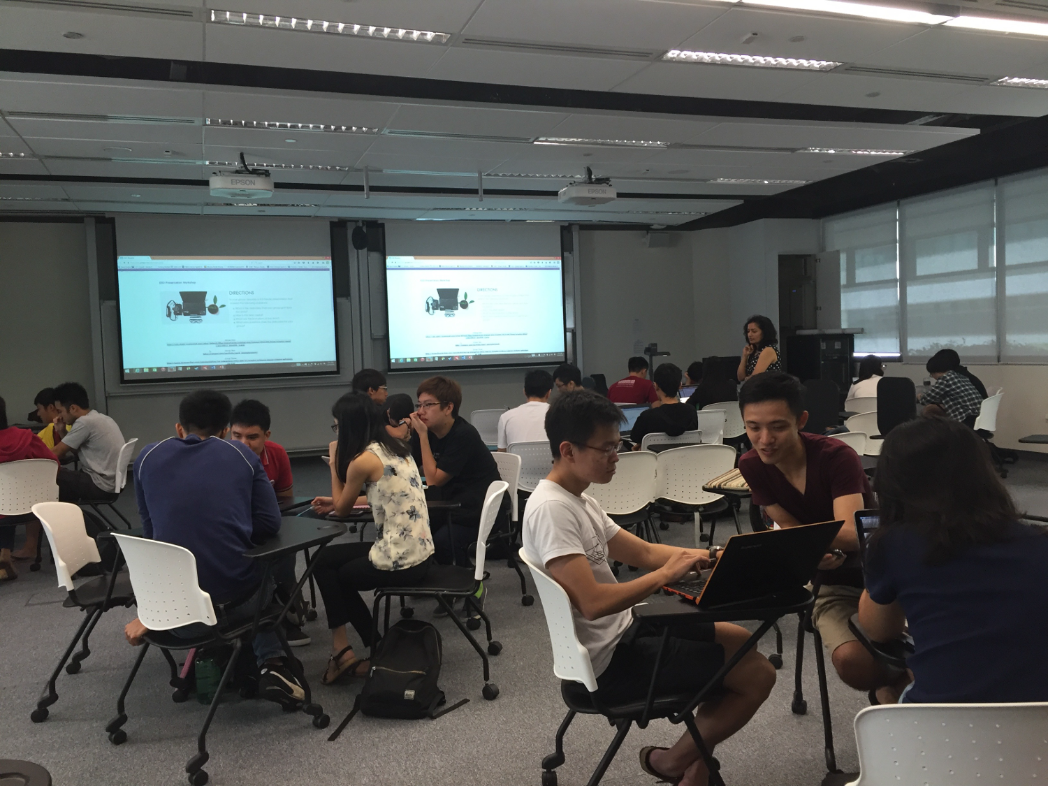 Students discussing in groups at tables during a workshop