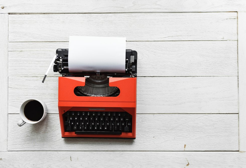 red and black typewriter near white ceramic mug with coffee