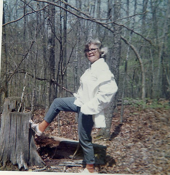 My grandmother stands in the woods with her leg on the stump. She looks confident.